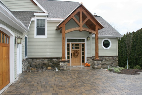 This home was expressly designed with a level threshold entry to address the needs of the owners. The wood front door includes matching sidelights and a transom window. Stone veneer was applied to the base of this home's front entryway and to the base of the columns that support the stylish custom overhang.
