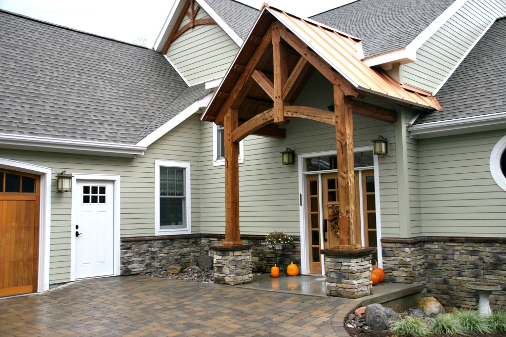 This home's entryway features a large post and beam portico with copper roof. Note that the portico design is replicated on the home's front roof peak.