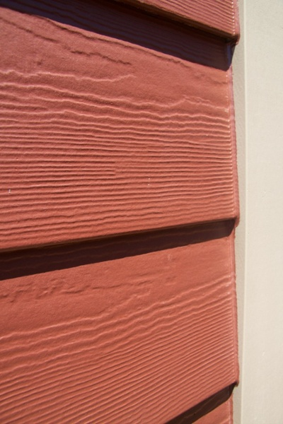 Close-up of fiber cement siding in rustic red with tan trim.
