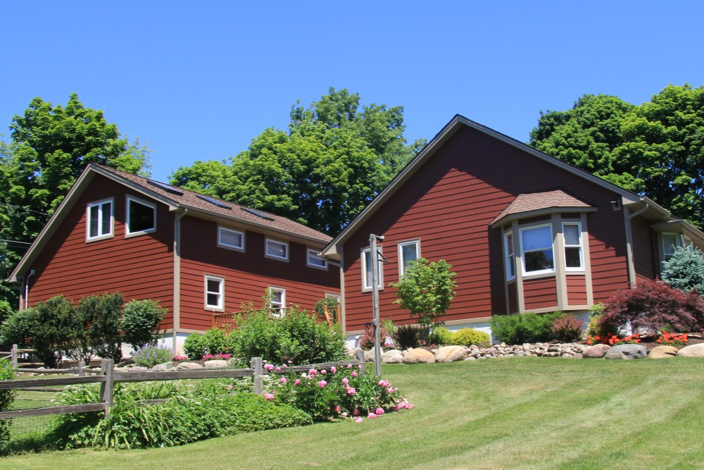 The exterior of these adjoining homes is fiber cement siding in rustic red with tan trim.