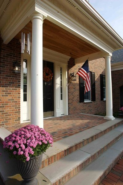 This attractive entry includes an overhang supported by tapered round columns, decorative trim above the door and fascia, and three steps on all sides of the brick porch.