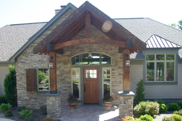 This exquisite front entry features stunning post and beam architectural details. The front door is made from larch wood. The sidelights and transom window has mission-style grids that complement the front door glass.