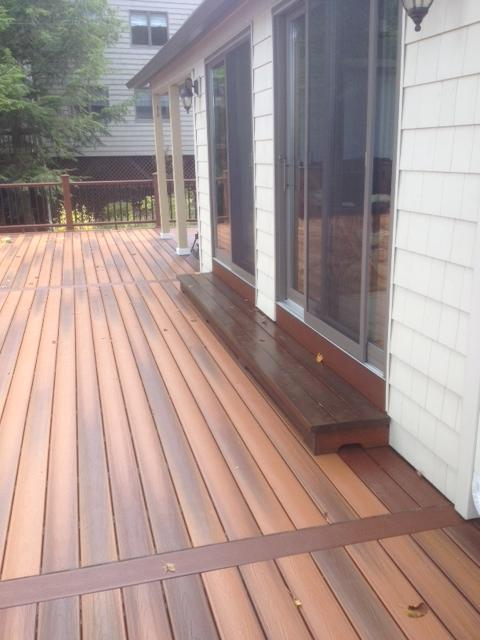 This composite deck has posts that support an overhang creating a shaded open porch for seating.