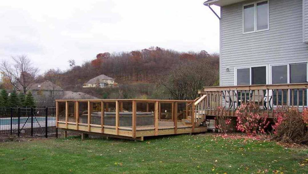 This deck was built around the whirlpool for easy access. Clear panels allow full view between railing posts.