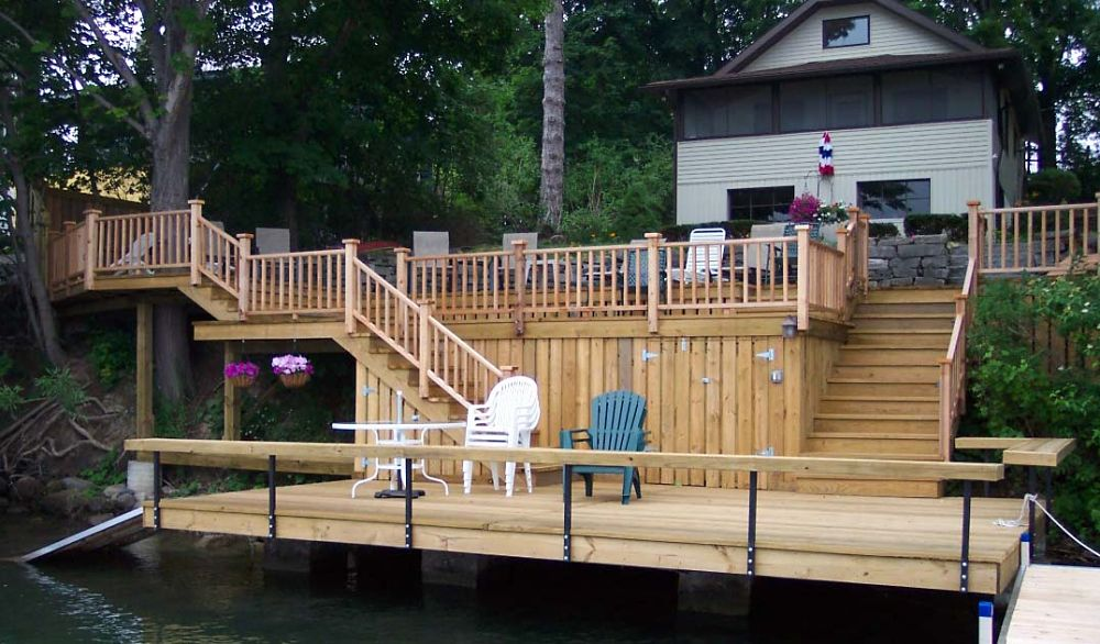 This deck over the water includes concealed storage areas, a ramp into the water and an attached dock with a cut-out for an existing tree. Benches incorporated into the deck design provide plenty of seating.
