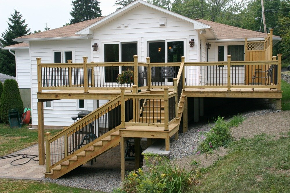The features of this elevated deck addition include two areas for outdoor living, a shelter and a patio surround for a hot tub. A privacy screen was added to the upper level deck.