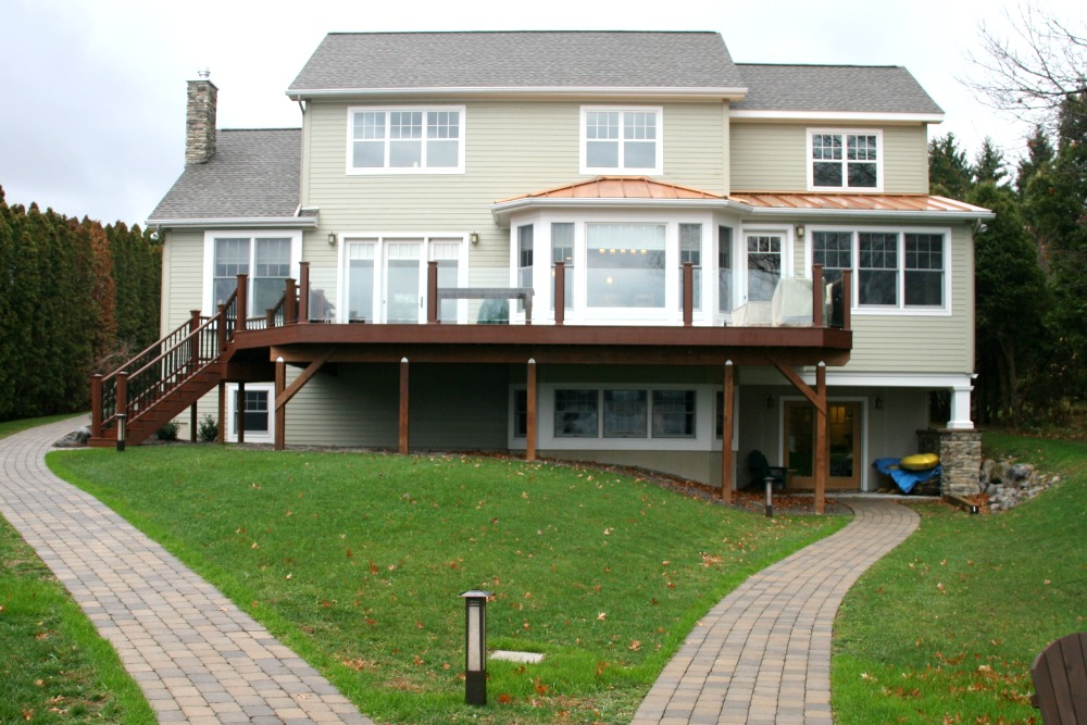 The back of this home faces Skaneateles Lake and has a raised deck constructed with DuraLife decking and glass panels to optimize the view. Building code requires that deck rails be at eye level when a person is seated. Since solid rails would obstruct the view for a person seated in a wheelchair, a special impact resistant safety glass railing was used with the glass panels. There is a lower level exit from the home to a pathway that leads to the dock. Windows and glass doors were strategically installed to provide a view of the lake from the interior.
