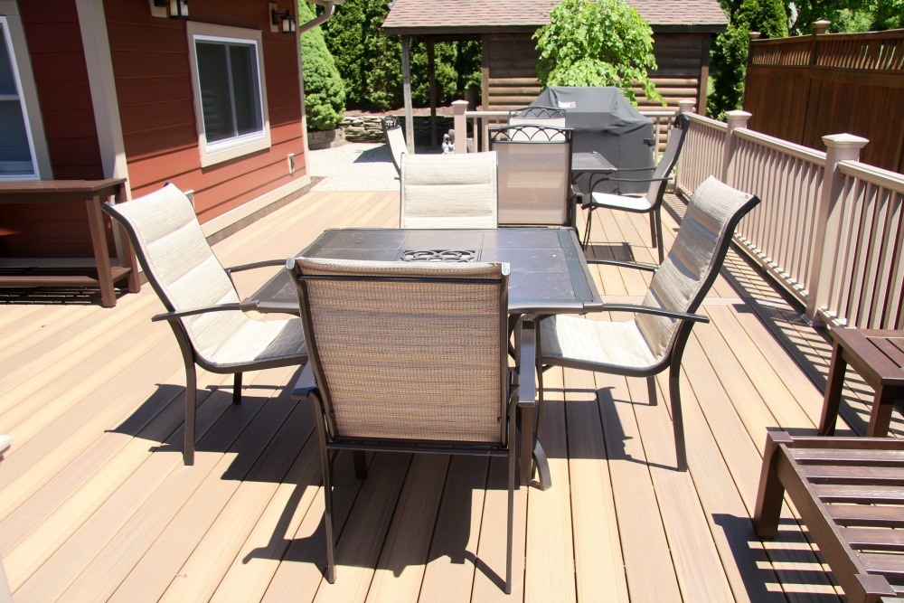This composite deck addition provides ample space for entertaining. The deck easily accommodates two outdoor dining tables, bench seating and a grill. The deck blends into two patio areas.