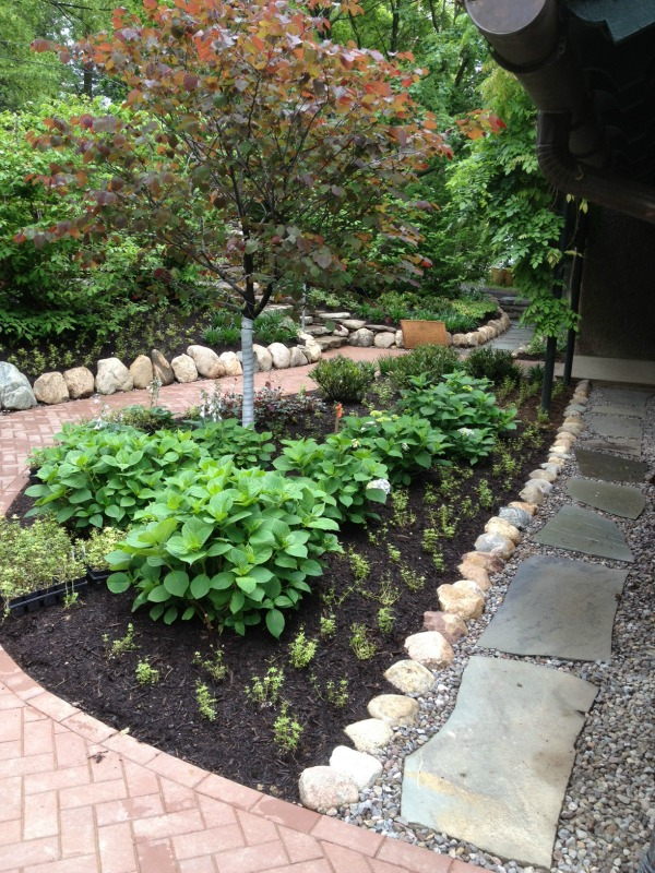 This landscaped garden space features a brick paver walkway and a blue flagstone walkway.