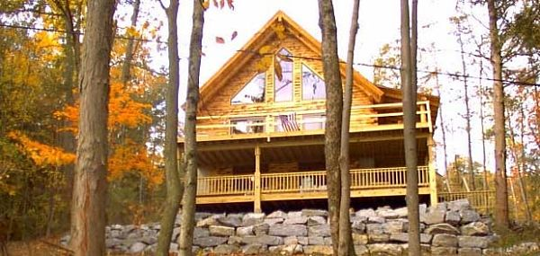 This Adirondack style log cabin features a two-level wrap around deck and a stone retaining wall. Large windows allow the owners to take in the view and bring light to the interior.