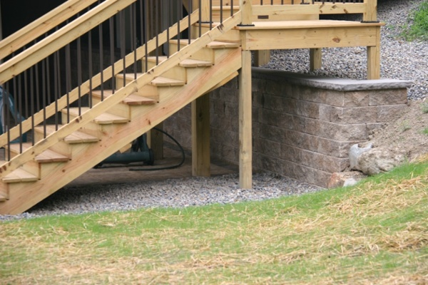 Extensive excavation was done to build the lower patio over an elevated deck. We installed a 30-by-4 inch high retaining wall to keep the unexcavated area in place. We used a