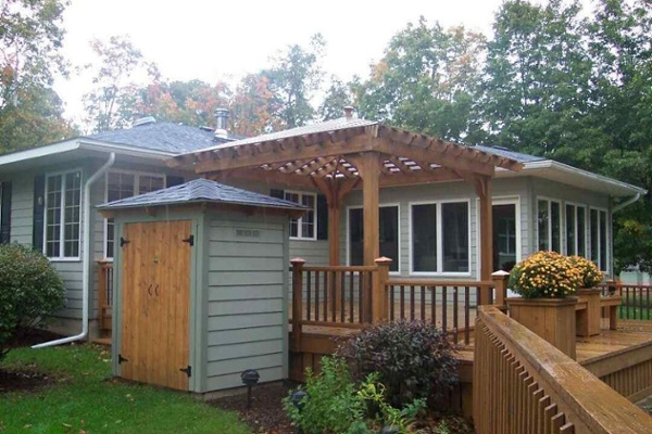Sunshine or rain the covered pergola offers an attractive living space on the deck. A small storage building provides storage for outdoor tools and houses the in-ground pool's pump and heater.