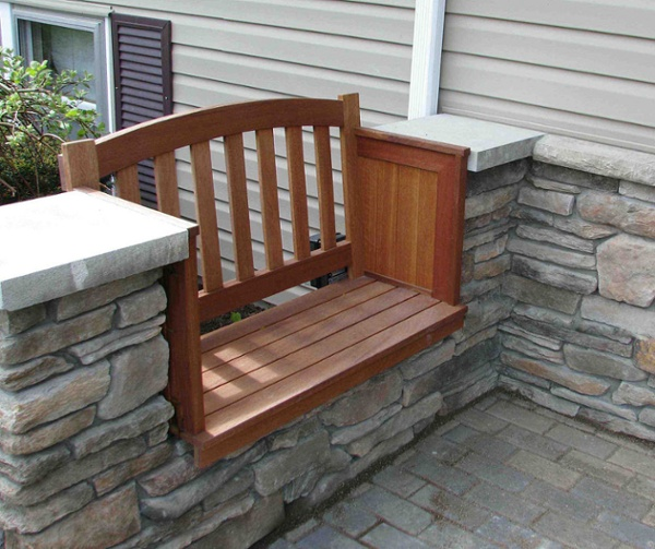 Custom built with mahogany, this built-in bench provides comfortable seating on this masonry front porch.