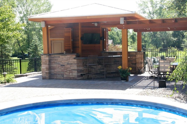This outdoor living space was designed expressly for a home with an existing pool and hardscape. The structure is an open pavilion with an attached pergola area for dining. The pavilion features a grill, a two-tier counter with bar seating for four, a storage closet for pool items, custom shutters and a metal roof.