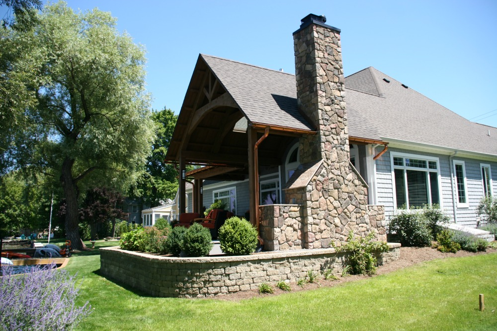 The gabled roof complements the shape of a large arched window and does not obscure the view of the outdoors. Boral cultured stone veneer was used on the chimney and the areas for built-in appliances and storage. Copper gutters were used for both function and aesthetics.