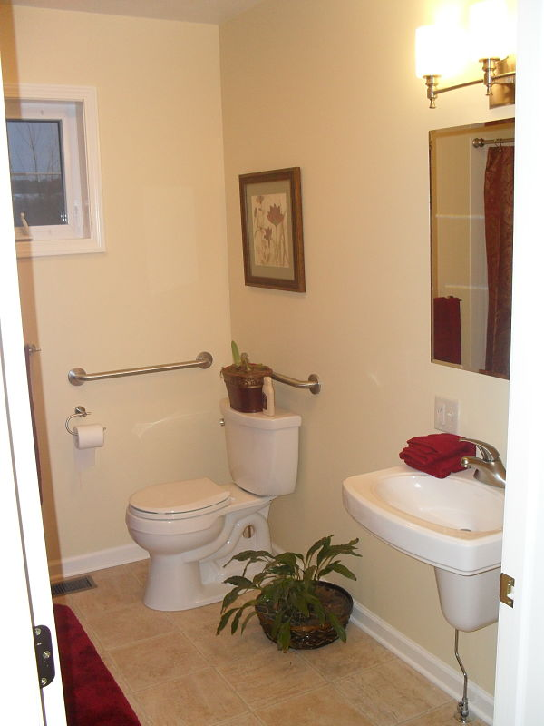 This bath features a wall hung sink and grab bars around the toilet.