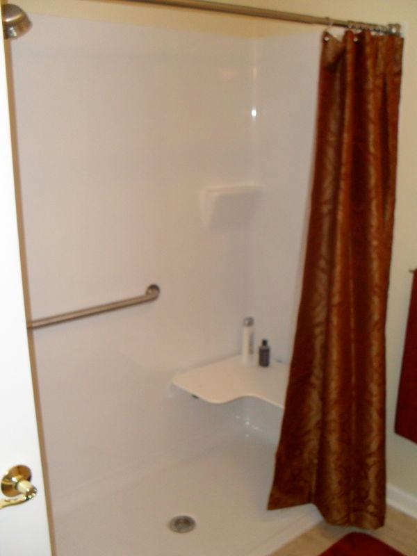 Fiberglass shower with built-in seat and grab bars.