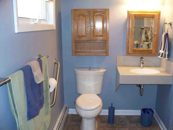 This bathroom includes many universal design elements such as grab bars, a wall mounted sink accessible to someone in a wheelchair, a chair-height toilet, a single handle faucet and products that are easy to clean such as the one piece sink.
