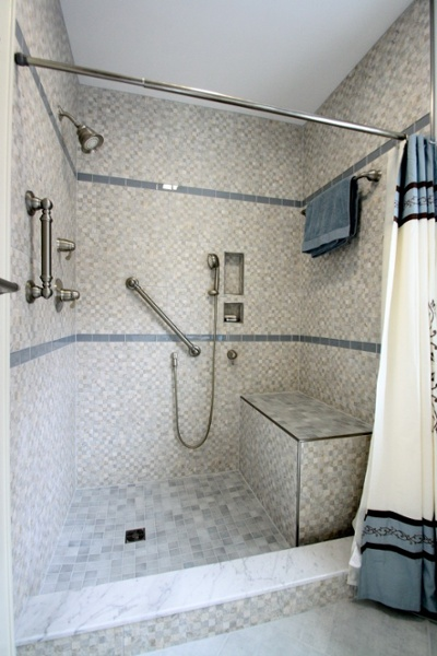 The custom tile base for this walk-in shower was designed to be integrated with a shower seat. Note the length and height of the threshold. Universal Design features include grab bars, lever-handle faucets, a large seating area and a hand-held showerhead with faucet mounted to be controlled while seated.