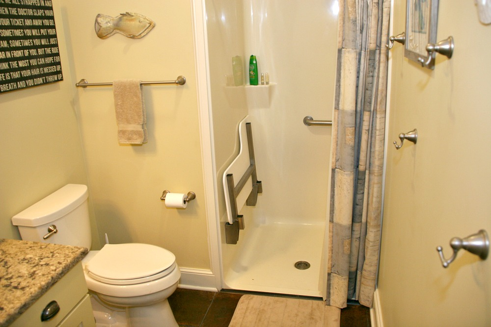 This walk-in shower in a small bathroom has a low threshold and a drop-down shower seat.